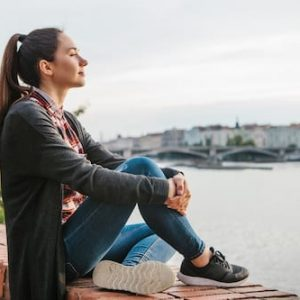 Young beautiful girl on the bank of the Vltava river in Prague in the Czech Republic, admiring the beautiful view and dreaming.