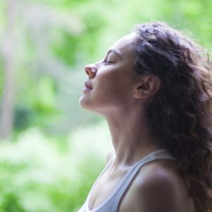 Young woman enjoying yoga, relaxing, feeling alive, breathing fresh air, calm and dreaming with closed eyes, in public park