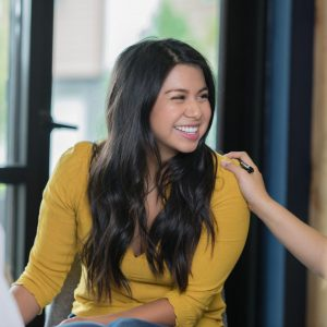 Beautiful Hispanic young adult woman is smiling during a support group therapy meeting. Unrecognizable woman is placing her hand on shoulder to offer support.