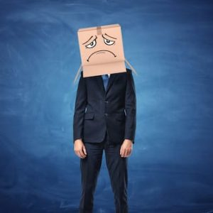 Business man with Box on his head with a sad face