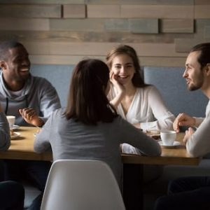 Diverse happy friends having fun sitting in cafe